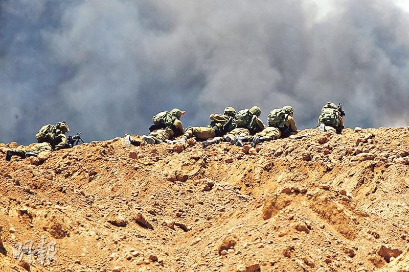 全副武裝以色列軍人(前)昨日在接壤加沙邊境,臥地準備迎擊巴人示威者。當日以軍用實彈鎮壓,造成巴人最少50死逾千傷。