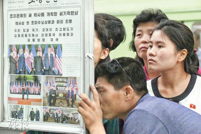 朝鮮官方媒體昨日圖文並茂報道美朝峰會,吸引不少民眾在平壤地鐵站內的報紙公告欄駐足細閱。
