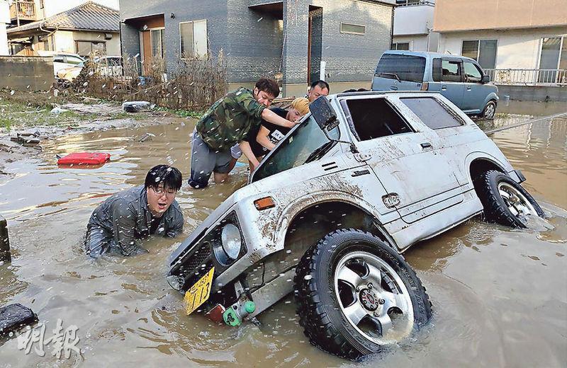 日本岡山縣倉敷市居民昨在依然水浸的街頭,想把翻側的車輛推正