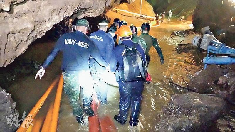 救援人員在滿是積水和泥濘的路上小心翼翼行走。