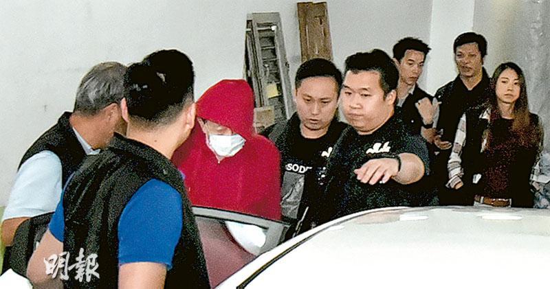 身穿紅色風褸、戴口罩的李宏邦,經通宵調查後被警方拘捕,昨午2時許被探員帶署調查。(林智傑攝)