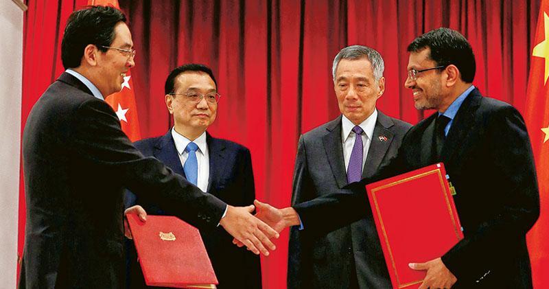 中國總理李克強(左二)和新加坡總理李顯龍(右二)昨見證中星簽署《自由貿易協定升級議定書》,被指大幅提高雙方貿易便利化水平。(路透社)
