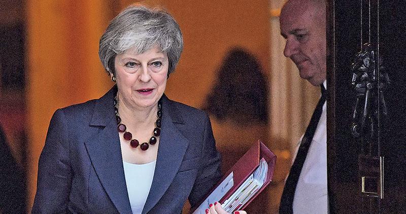 英國首相文翠珊周三(14日)帶着一疊文件走出唐寧街10號相府,準備出席國會每周例行答問會。(法新社)