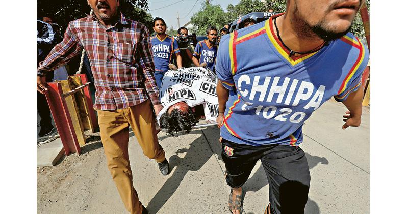 巴基斯坦救援人員昨從遇襲的中國駐卡拉奇領事館抬出一具屍體。(路透社)