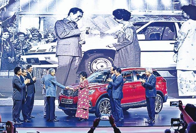 中國與大馬近期經濟合作頗多,國產汽車品牌吉利及大馬品牌寶騰上周舉行發布會,大馬首相馬哈蒂爾(左四)將車匙交給妻子茜蒂哈斯瑪(右四),熒幕重現1985年首輛寶騰下線時的情形(後方黑白圖片)。(新華社)