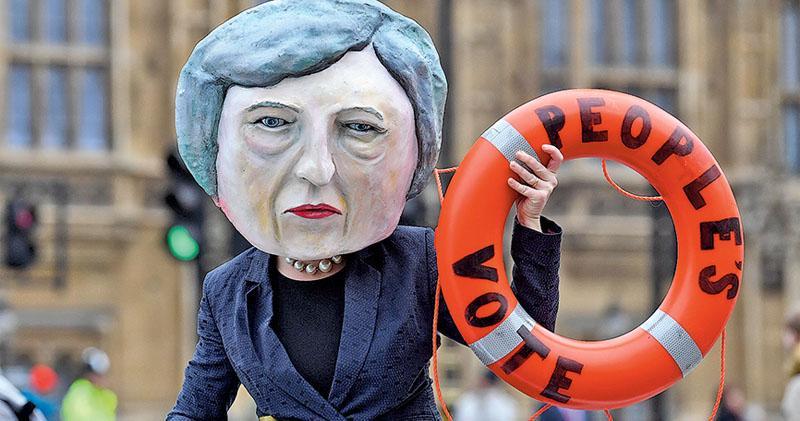 一名要求舉行第二次公投的示威者昨在國會外扮成拿着救生水泡的首相文翠珊,要求讓選民決定國家未來。(路透社)