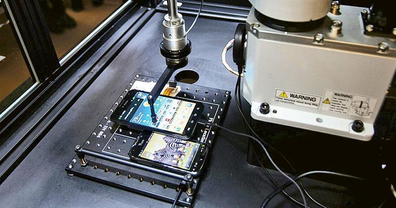 圖為T-Mobile用於測試手機的機械人,手指狀的尖端模擬人手觸碰手機屏幕,華為被指竊取相關技術。(網上圖片)