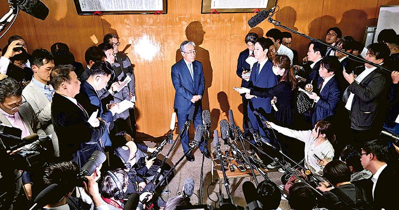 日本奧委會主席竹田恒和(中)在日本奧委會會議後見記者,回應不會連任主席的提問。(法新社)