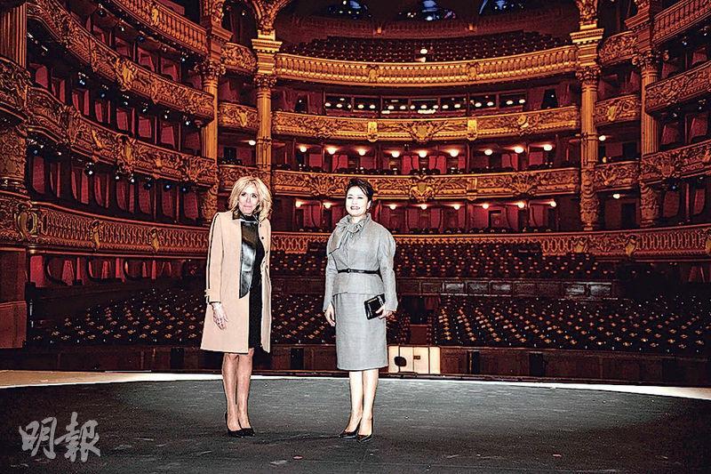 國家主席習近平夫人彭麗媛(右)周一(25日)在法國總統夫人布麗吉特(右)陪同下,參觀位於巴黎市第九區的法國巴黎歌劇院。彭麗媛先後參觀了歌劇廳和舞蹈排練廳,欣賞男中音和女高音歌唱家演唱《魔笛》、《唐璜》等莫扎特經典歌劇選段,並與布麗吉特走上舞台與演員交流。巴黎歌劇院建於1875年,擁有享譽世界的芭蕾舞團和管弦樂隊。(法新社)