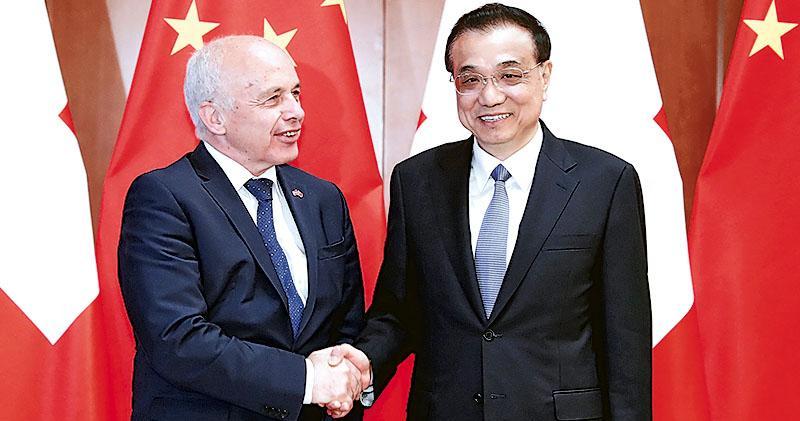 李克強(右)昨會見瑞士聯邦主席毛雷爾(左)時表示,願將「帶路」倡議同瑞士發展戰略對接,以及盡快開啟自貿協定升級談判進程。(新華社)
