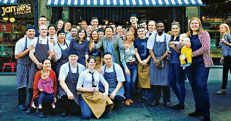 英國名廚奧利佛(第二排左六)旗下的英國連鎖餐廳已被會計師行接管,逾1300名員工或面臨被裁員的風險。圖為2015年10月,奧利佛去到蘇格蘭阿伯丁的連鎖意大利餐廳「Jamie's Italian」視察,與一眾員工合照。(網上圖片)