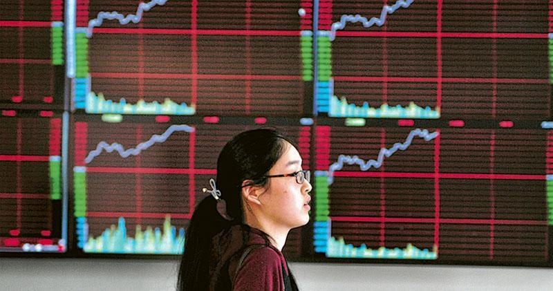 中港股市昨日炒作稀土概念,滬指升逾1%,但港股無法維持升勢,倒跌收場。圖為內地市民從股票顯示屏前經過。(中新社)