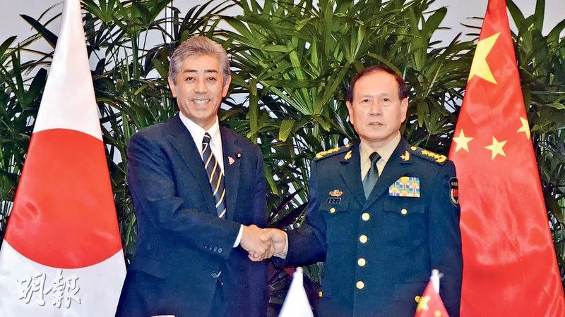 國防部長魏鳳和與日本防衛大臣岩屋毅前日在出訪地新加坡會談,一致同意為盡早開設防衛部門幹部間的熱線而加速協調。圖為魏鳳和(右)和岩屋毅在會談前握手。(網上圖片)