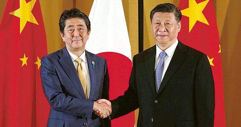 國家主席習近平昨日傍晚與日本首相安倍晉三會晤,並共晉晚餐。圖為會晤前,習近平(右)與安倍握手時,兩人面帶微笑。(路透社)