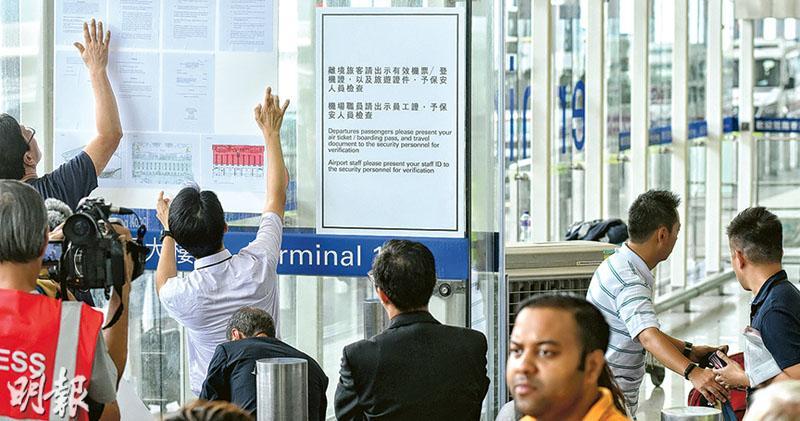 執達吏在機管局職員協助下,昨午約2時半,在1號客叽髽请x港層落客區入口外,貼出法庭臨時禁制令(左),表明禁止任何人非法及有意圖故意阻礙或干擾機場的正常使用。右邊有告示提醒離境旅客出示「有效機票/登機證,以及旅遊證件,予保安人員檢查」。(蘇智鑫攝)