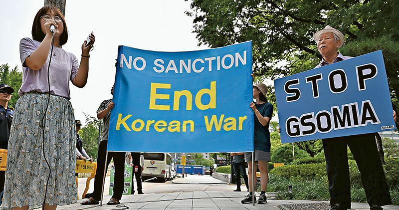 韓國首爾有反戰社運人士周三趁美國國務院朝鮮問題特別代表比根到訪外交部時抗議,舉起終止韓戰、停止制裁,和停止《韓日軍事情報保護協定》(GSOMIA)的標語牌。(法新社)