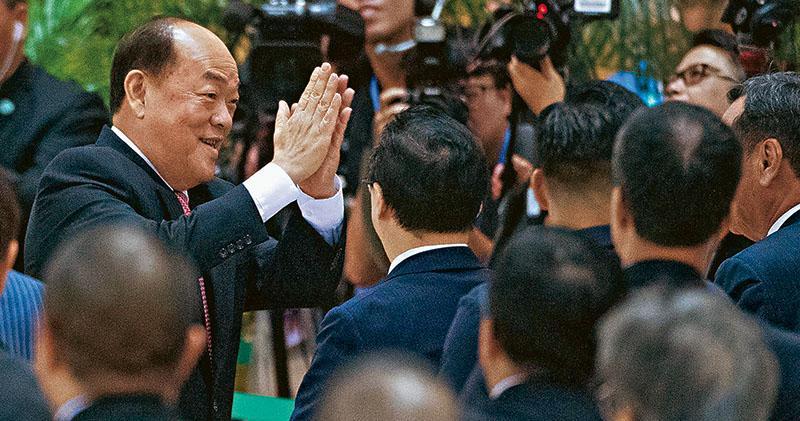 澳門前立法會主席賀一誠(左)在無對手下,以392票當選第五任澳門行政長官,隨即向台下選委謝票。(新華社)