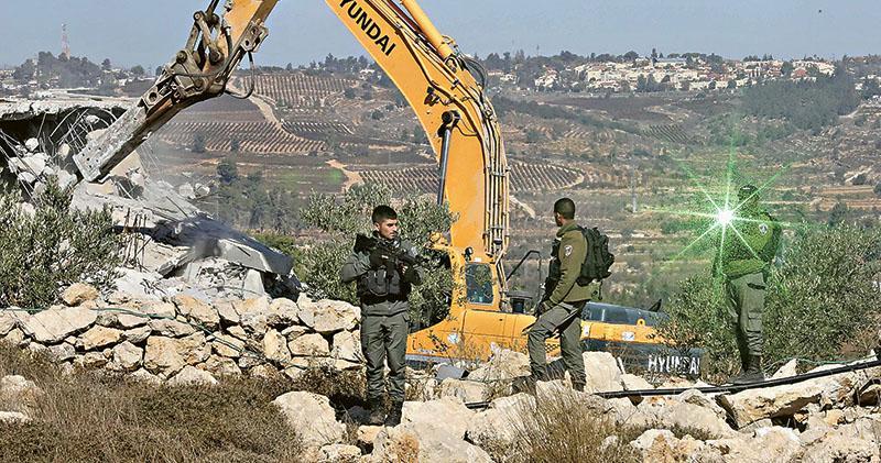 以色列人員昨日在西岸城鎮希伯倫用推土機拆除巴人房屋,有以色列軍人持槍戒備,並以激光電筒照向記者的鏡頭。(法新社)
