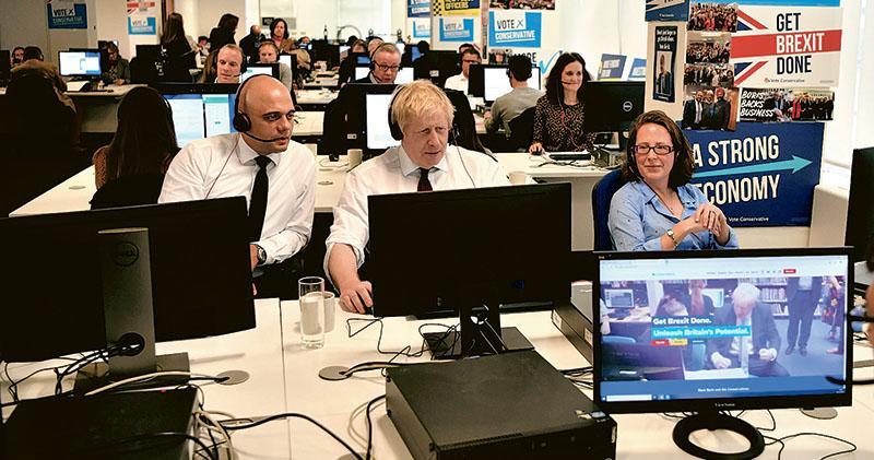 英國財相賈偉德(前左)、首相約翰遜(前中)、上議院領袖歐樂怡(前右)及外相藍韜文(次排左)等官員昨在保守黨競選總部接聽電話,加緊拉票。(法新社)