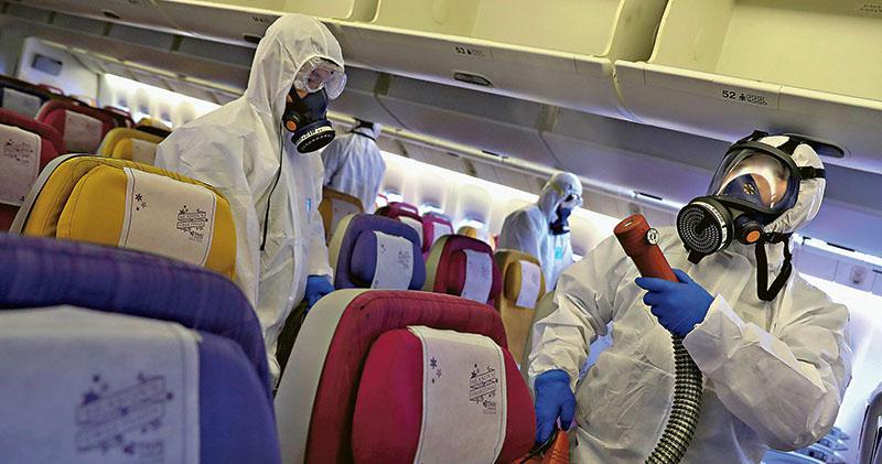 泰國國際航空職員昨日穿上全副裝備,為停泊在曼谷蘇凡納布機場的飛機消毒,避免新型冠狀病毒傳播。(路透社)