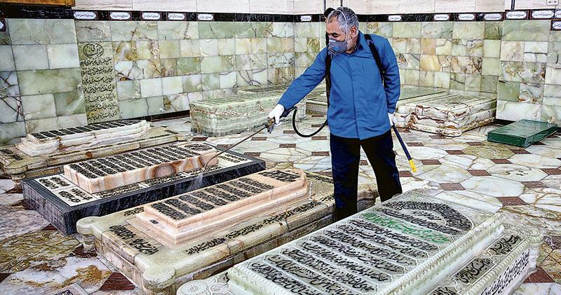 伊朗聖城庫姆爆發新型冠狀病毒肺炎,工作人員昨天為當地名勝之一的法蒂瑪聖陵消毒。(法新社)