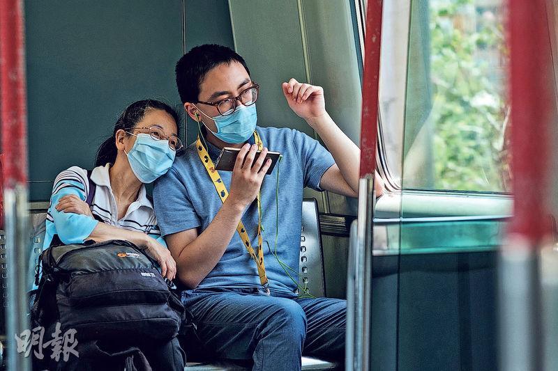 患有嚴重自閉及輕度智障的康愉(右)最喜歡乘搭交通工具外出,疫情下停課,他不習慣長期困在家。儘管擔憂疫情,61歲的康愉媽媽(左)還是堅持每朝收拾行裝,與兒子乘坐不同交通工具漫遊香港。上車後,媽媽會給康愉手機,讓他一邊看YouTube影片,一邊看窗外風景。(賴俊傑攝)