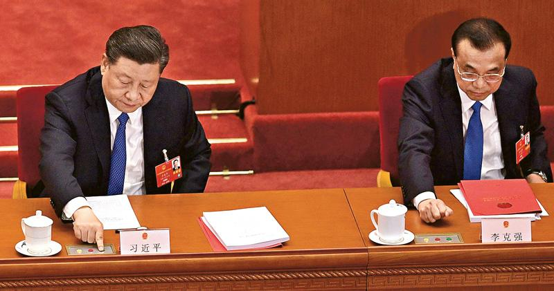 全國人大會議昨日表决《全國人民代表大會關於建立健全香港特別行政區維護國家安全的法律制度和執行機制的決定(草案)》,國家主席習近平(左)、總理李克強(右)按下表決鍵。該決定最終以2878票贊成、1票反對、6票棄權獲得通過。(路透社)