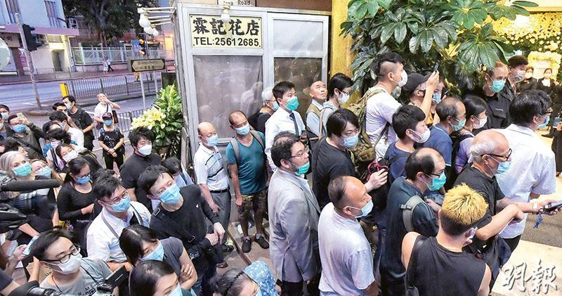 昨日香港殯儀館的何鴻燊設靈處,排隊等候的公眾、中外傳媒及各界送上的花牌,全部夾雜其中,有到場弔唁的公眾說能拿到場刊留念,並謂到過何經營的賭場下注「賭幾手」。由於不少排隊致祭的市民早在中午12時開始等候,至下午6時卻仍未能進場,一度引起鼓譟。(劉焌陶攝)