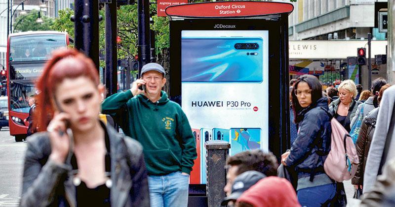 英國政府昨日下令電訊服務供應商在明年起禁買華為的5G設備,2027年前拆除現有的華為設備。圖為倫敦市中心去年4月的華為廣告板。(網上圖片)