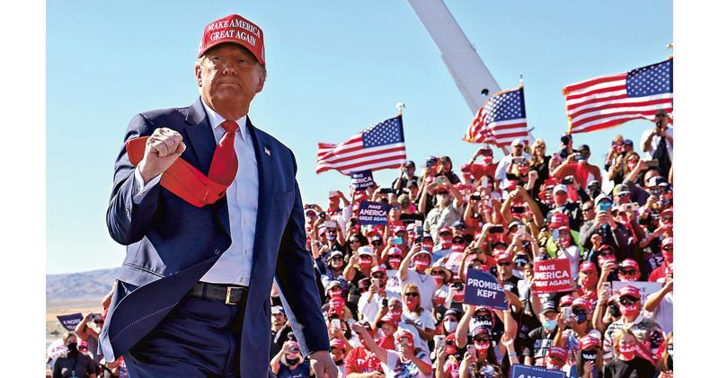 爭取連任的美國總統特朗普(前)周三出席關鍵游離州亞利桑那州布爾黑德城的造勢大會,其間他向支持者舉拳致意。(路透社)