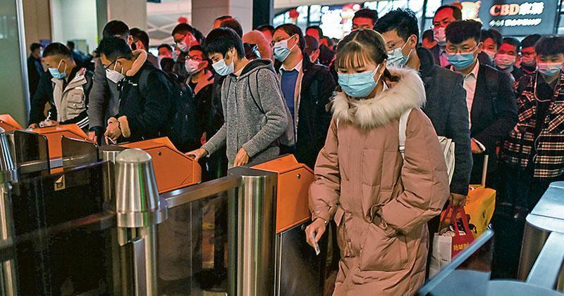內地專家稱目前疫情呈物傳人和人傳人並存的情况。圖為昨日在湖北武漢,戴着口罩的乘客進入地鐵站。(法新社)