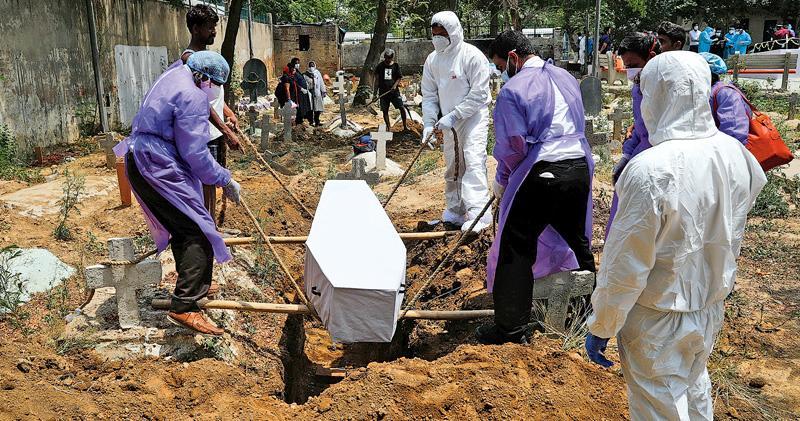 昨在印度新德里一處墓園,工作人員穿著全副保護衣物準備埋葬一具新型冠狀病毒死者的遺體。(路透社)