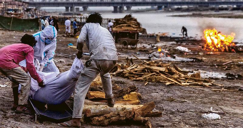 印度近日有多具懷疑是新冠死者的遺體被冲上恆河河岸,相信來自北方,引發地方政府關注。圖為北方邦本月初有民眾把新冠染疫死者的遺體搬到恆河邊的火葬場。(路透社)