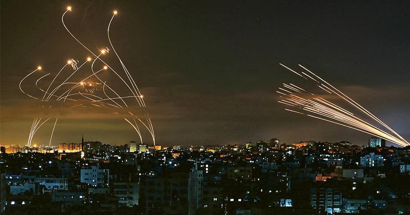 巴勒斯坦武裝組織哈馬斯周五凌晨再次從加沙地區向以色列發射火箭炮(右),以色列則以「鐵穹」防空系統發射飛彈(左)攔截。以色列指「鐵穹」實戰攔截成功率高達九成,但哈馬斯嘗試以短時間密集發射多炮,部分得以漏網擊中以境導致傷亡。(法新社)