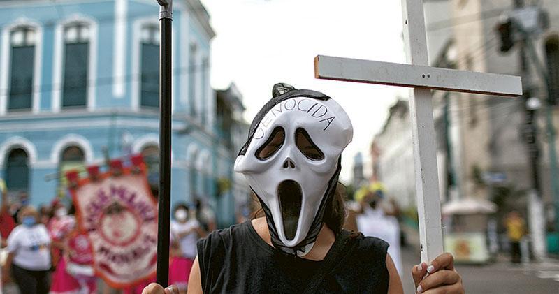 巴西亞馬遜州首府馬瑙斯(Manaus)上周六(19日)有民眾示威,抗議總統博索納羅應對新冠疫情手法,有示威者手持假鐮刀和十字架,戴着的面具上寫有種族滅絕字眼。(路透社)