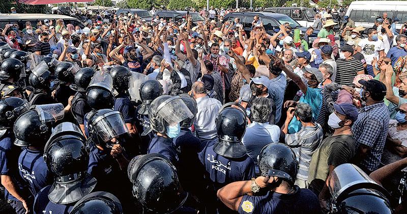 突尼斯保安當局人員周一(26日)在首都突尼斯市的國會大樓外阻擋面前大批示威者。(法新社)