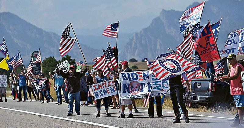 美國一群特朗普支持者周二在科羅拉多州阿瓦達的公路旁,向途經前往國立再生能源實驗室參觀的總統拜登示威,要求彈劾拜登。(法新社)