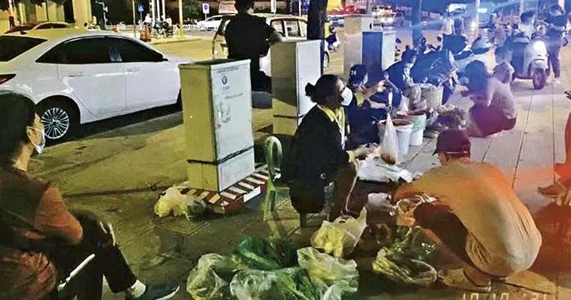 瑞麗市早前菜市場、超市關閉,居民要接受統一訂購的蔬菜價格。有居民自行在街上擺攤賣菜,但因避城管要在夜晚開檔。(受訪者提供)